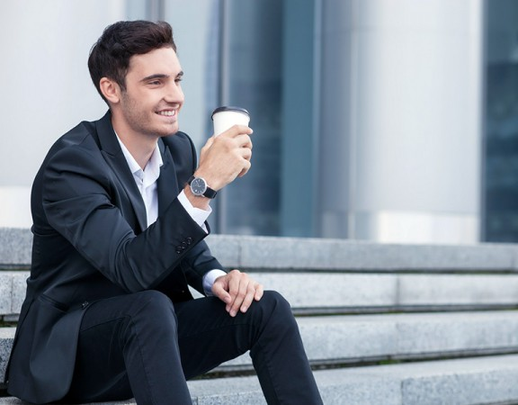 Attractive young businessman is sitting on steps outdoors. He is drinking coffee and smiling. The guy is looking aside with joy. Copy space in right side